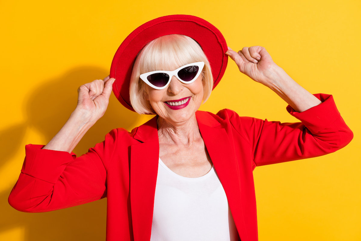 Photo portrait of happy senior lady wearing sunglass red hat smiling in blazer isolated on bright yellow color background