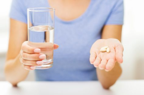 woman in blue crew neck t-shirt holding glass of water and handful of supplements