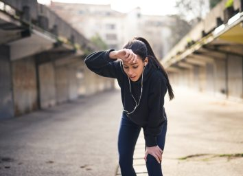 Woman wiping sweat from forehead after a heavy training.