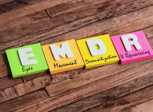 Colorful square papers with wooden white letters for the English acronym word, EMDR