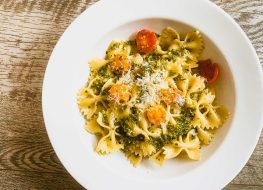 basil pesto mixed in with pasta and tomatoes and cheese