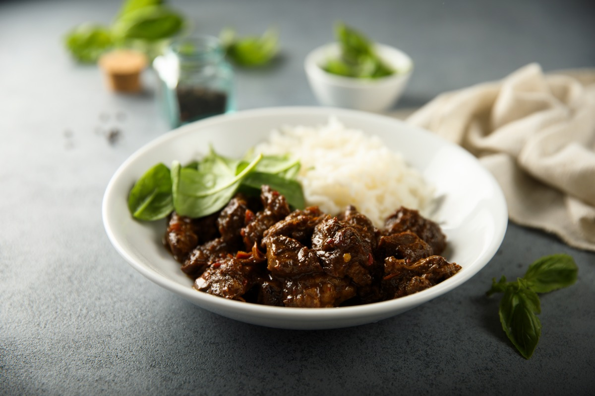 beef with rice and spinach in a white bowl