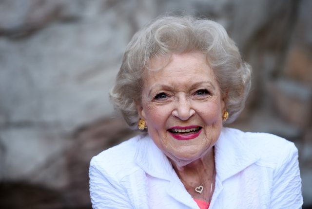 betty white laughing in white jacket and pink shirt