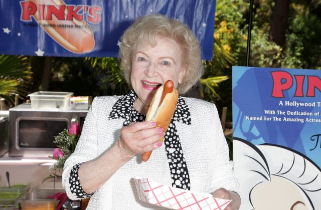 betty white holding a hot dog outdoors