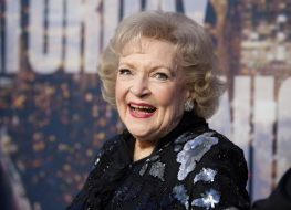 betty white laughing in black outfit on red carpet in front of snl step and repeat