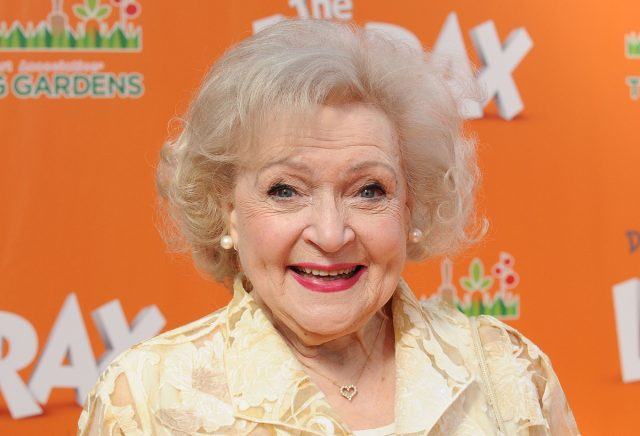 betty white smiling in front of orange step and repeat for the lorax