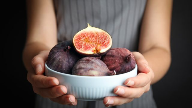 woman holding a bowl of figs