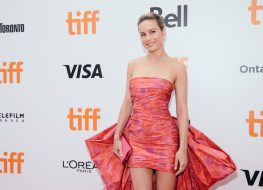 brie larson in a short pink dress with a large bow or train on the carpet at the toronto international film festival