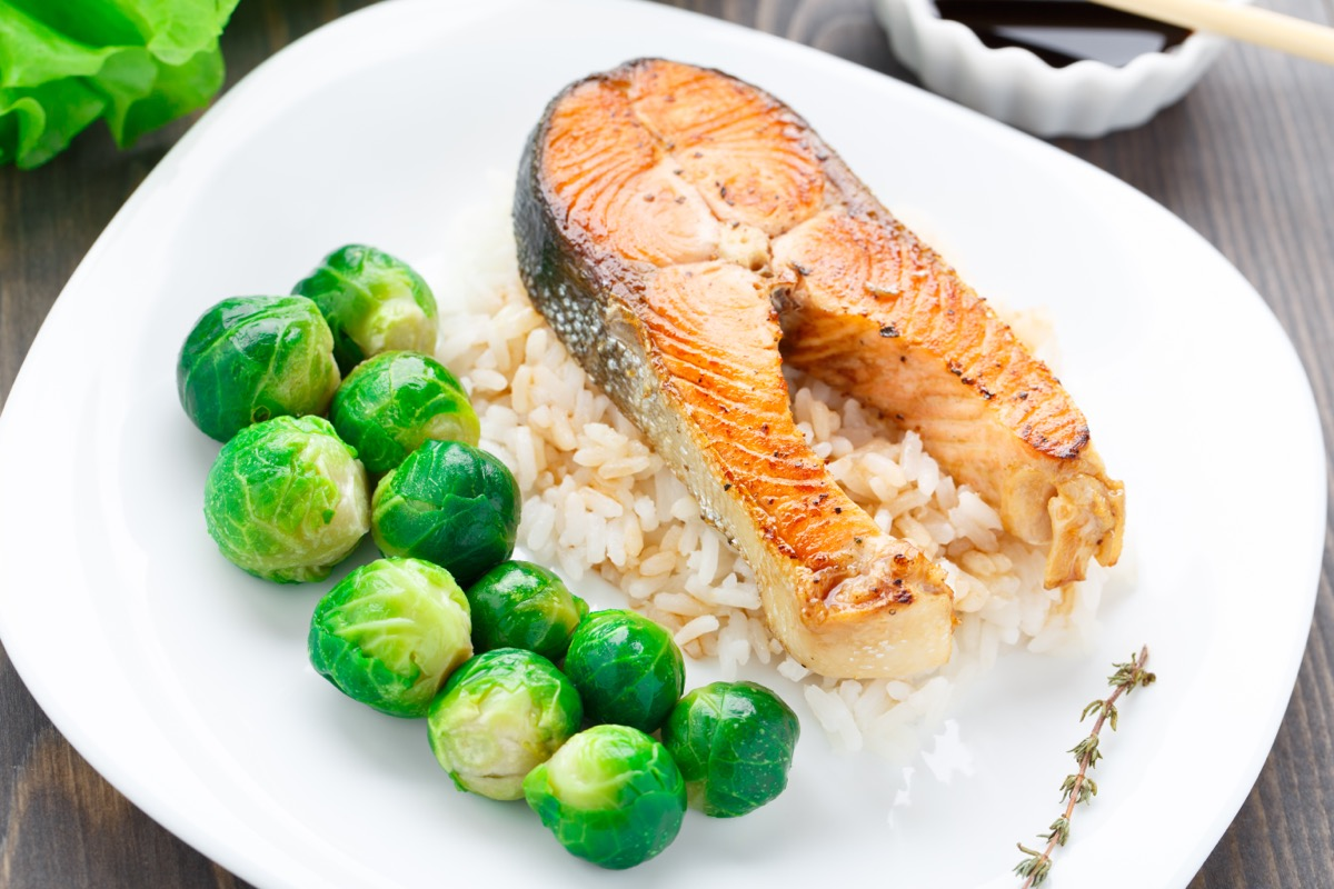 large salmon steak, brussels sprouts, and rice on white plate