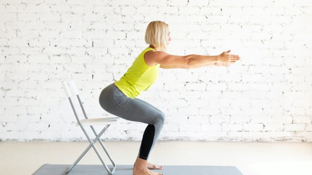 Yoga with a chair. Fit adult caucasian woman practice squat with props on a mat in loft white studio indoor, selective focus. Fitness, workout, trainer, sport, healthy lifestyle, concept.