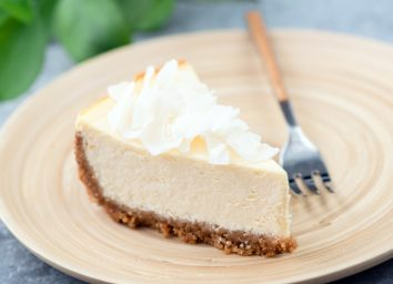 coconut cheesecake on cream colored plate next to fork