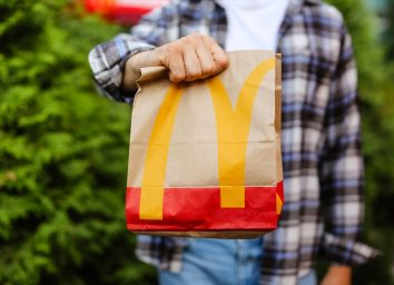 young man holding mcdonald's bag standing outdoors