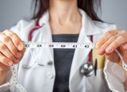 Doctor holding a tape measure in her hands which shows 40 inches as abdominal circumference.
