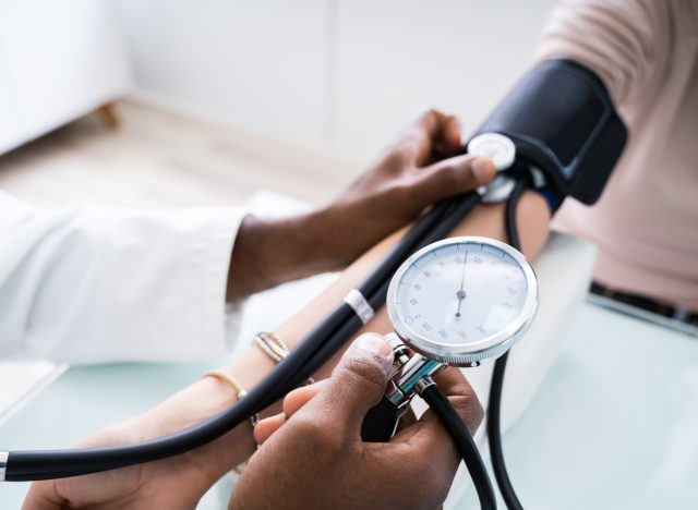 doctor taking patient's blood pressure with analog device