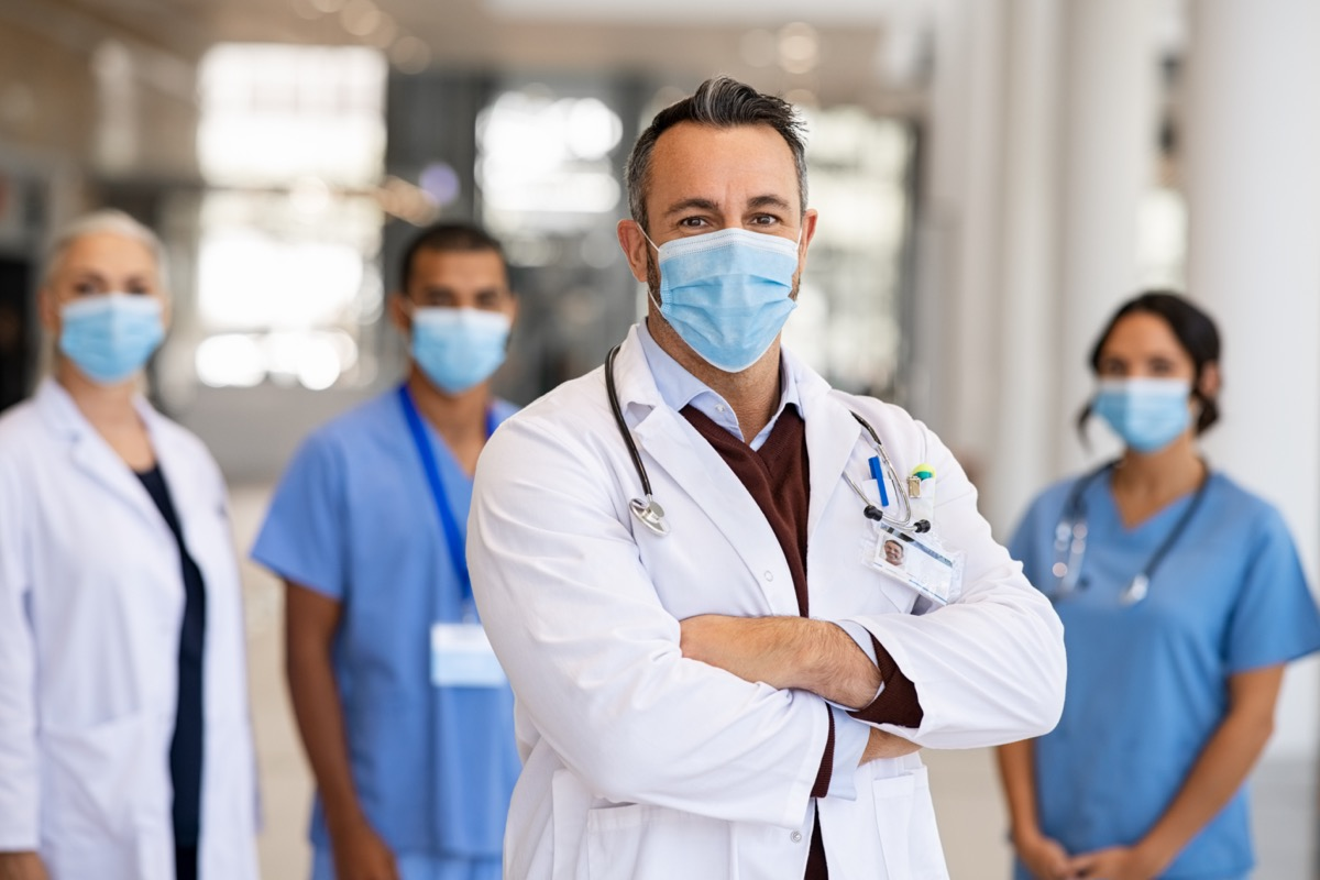 Mature doctor standing in hallway with medical team in hospital wearing surgical mask due to covid.  Smiling general practitioner with crossed arms looking at camera.