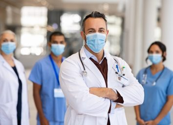 Mature doctor standing in corridor with medical team at hospital wearing surgical face mask due to covid. Smiling general practitioner with crossed arms looking at camera.