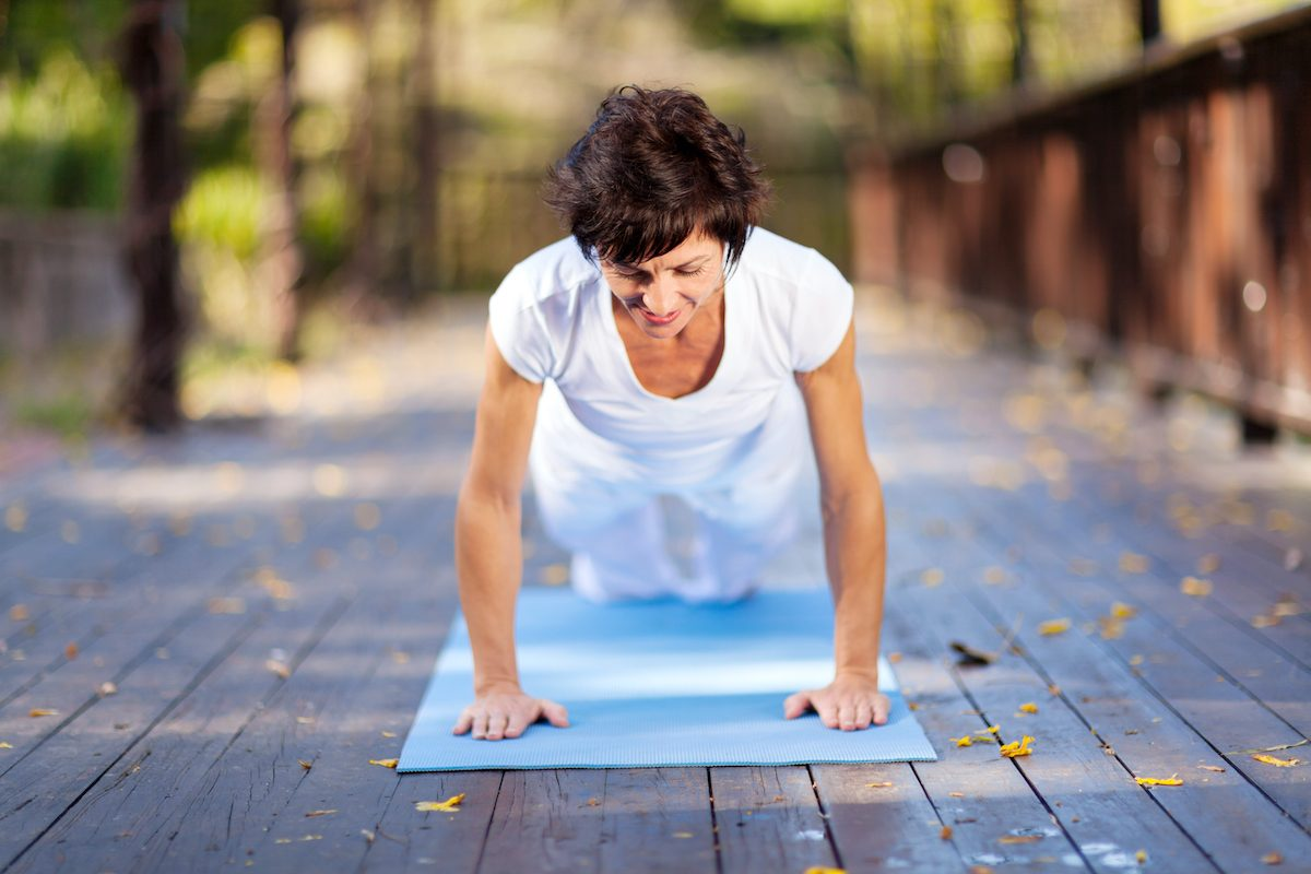 fit middle aged woman doing pushups outdoors
