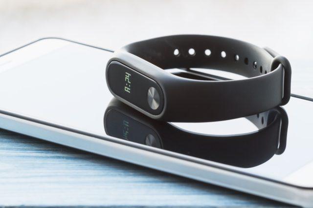 black fitness tracker sitting on on smartphone
