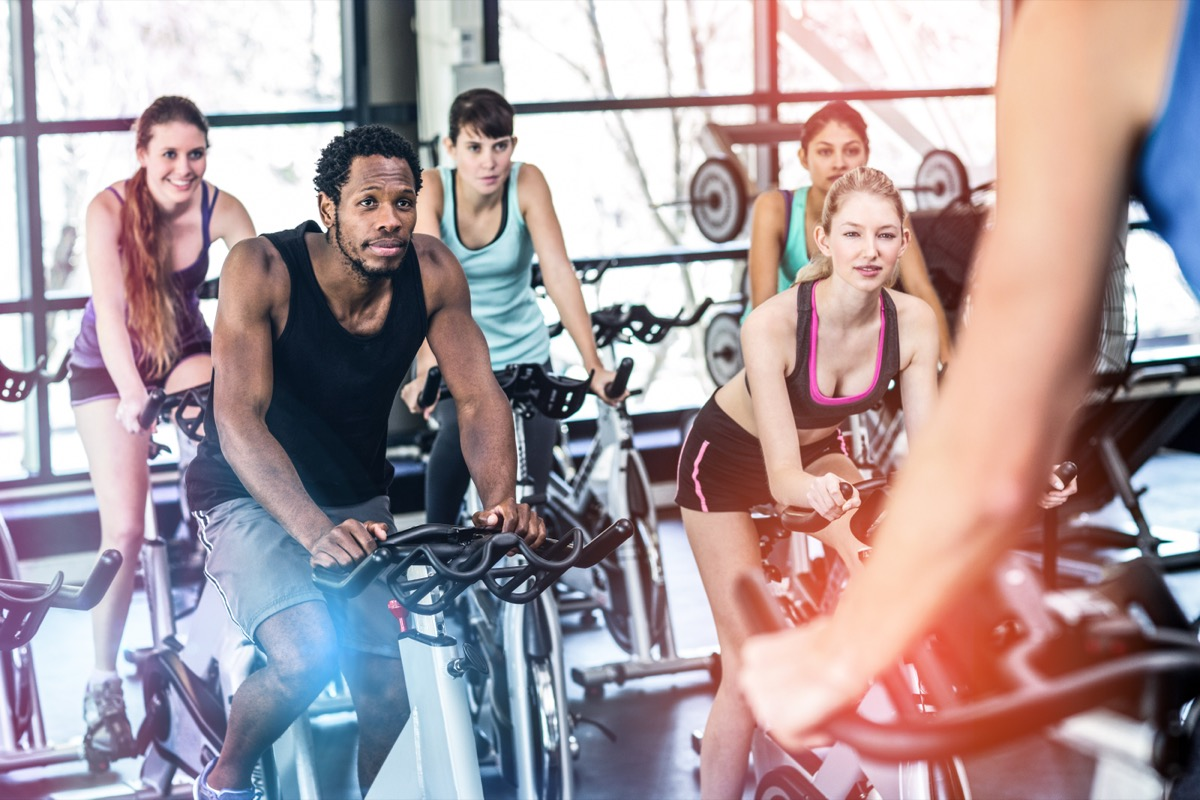 multiracial group of 20 or 30-something adults on bikes in an indoor cycling class