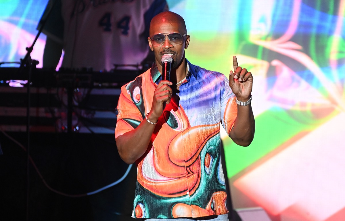 jamie foxx in colorful t-shirt holding a microphone and holding one index finger up while on stage