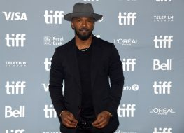 jamie foxx in black suit and gray hat on red carpet at toronto international film festival