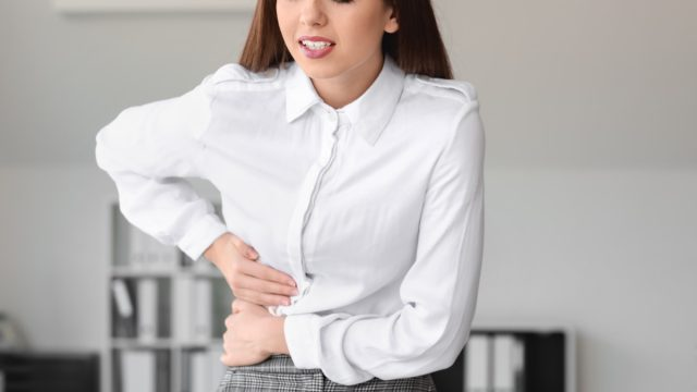 young woman in business attire experiencing liver pain