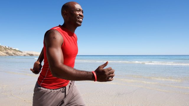 fit middle-aged man walking on the beach on a sunny day