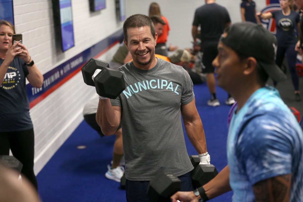 mark wahlberg doing dumbbell curls in a gym with other people
