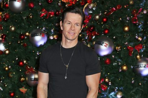 mark wahlberg in black t-shirt and cross standing in front of christmas tree