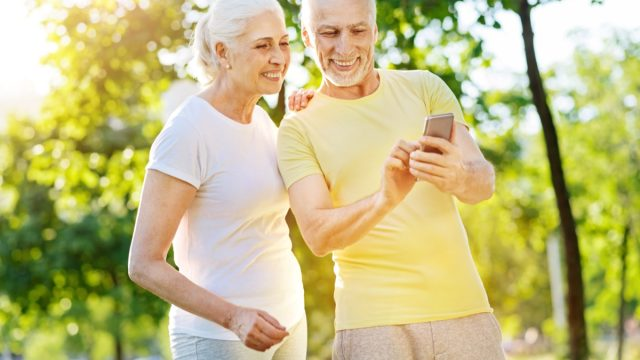 Happy mature couple looking at mobile phone in park.