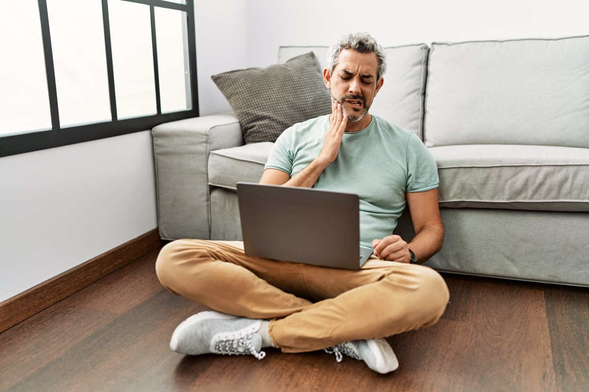 Middle age hispanic man using laptop sitting on the floor at the living room touching mouth with hand with painful expression.