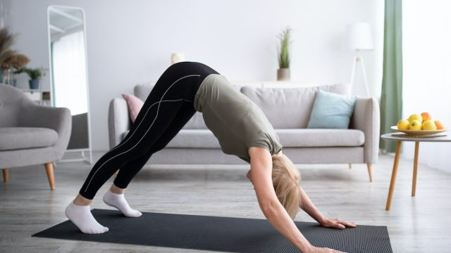 Domestic,Yoga,Practice.,Flexible,Mature,Lady,Standing,In,Downward,Facing