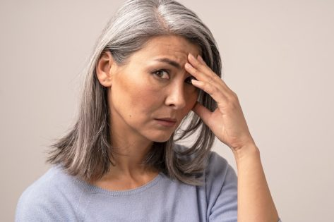 Sad mature woman puts her hand on her forehead.