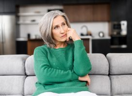 Mature woman with grey hair, thinking touching the face, looking aside, sitting on the pure sofa at apartment.