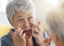 Mature white-haired woman checking eye wrinkles in front of mirror.