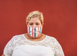 Curvy woman smiling on camera while wearing face protective mask outdoor