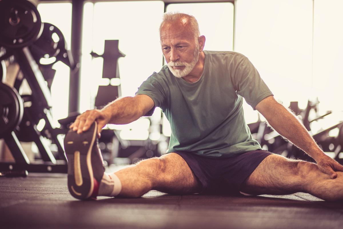 older man stretching in a gym