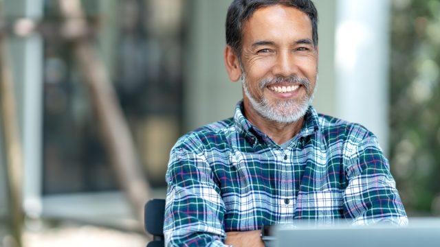 Older man using laptop smiling