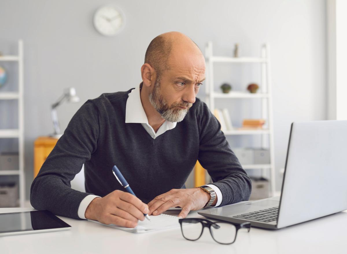 older man using laptop writing