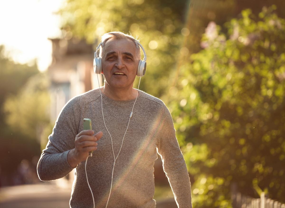 older man walking headphones