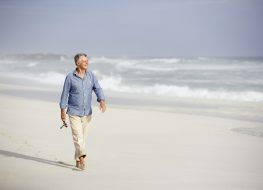 older man walking on the beach