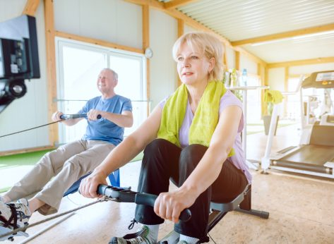 older woman man rowing machines