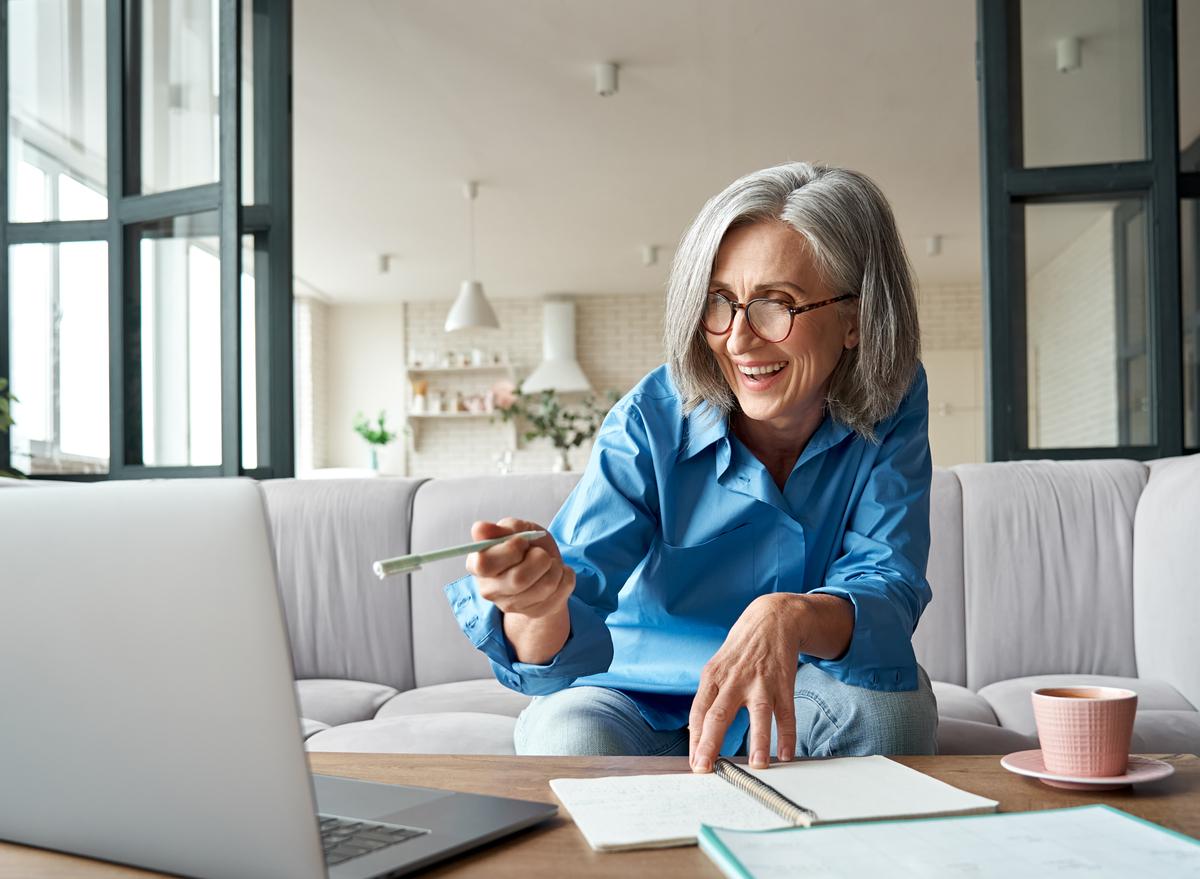 older woman smiling laptop working