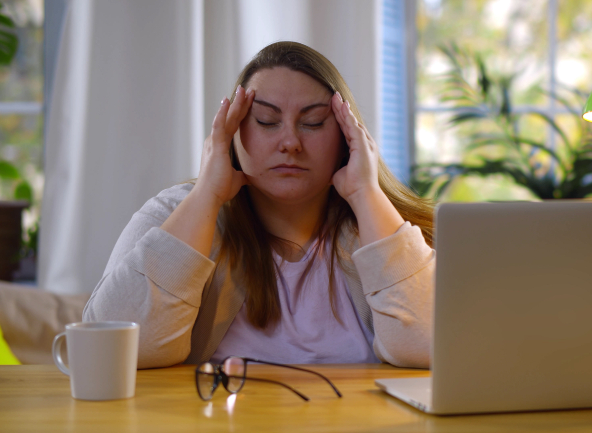 Tired overweight woman suffering eyestrain working on laptop at home