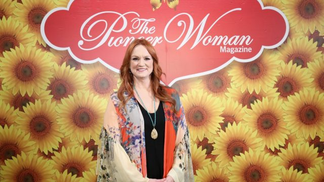 ree drummond in floral silk top standing against sunflower backdrop