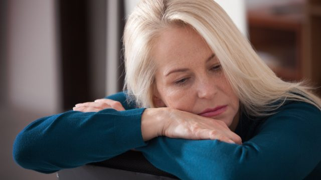 Sad depressed woman at home sitting on the couch, looking down and touching her forehead