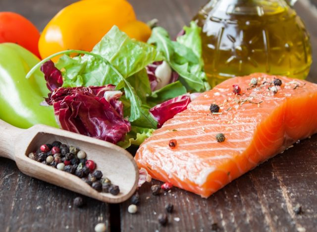 salmon, vegetables, and olive oil on wooden backdrop