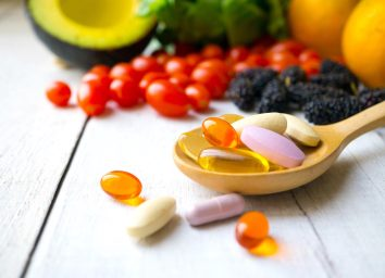 wooden spoon full of supplements with fruits and vegetables in the background