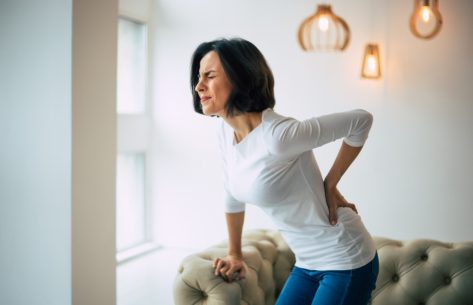 Woman is holding her lower back, while standing and suffering from pain.