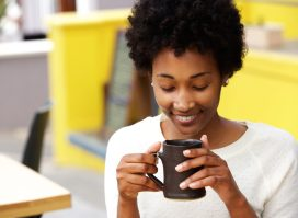 young woman with curly hair drinking from black mug